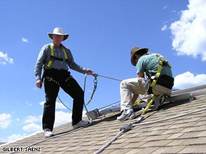 "Gilbert Saenz: ""I began learning about Solar installation in August 2006. A fellow student watches as I'm leaning over to set up the mounting of Solar Panels."""