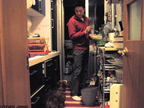 Beijing resident Alex Chen prepares dinner at home as his dog Charlie looks on.