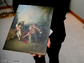 A Christie's employee holds the painting 'La Surprise' at Christie's auction house in London on July 4, 2008.