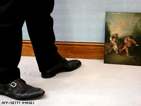 A Christie's employee stands beside a painting  at Christie's auction house in London on July 4.