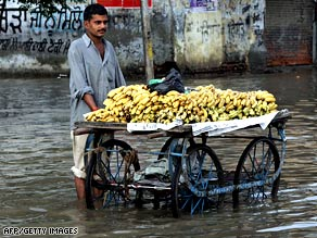A banana vendor stands on a flooded street as he waits for customers in Amritsar, India, on August 13.
