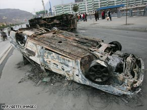 A wrecked car lies in the road following riots in Longnan over plans to relocate government offices.