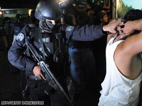 Police arrest a suspected MS-13 member during an April operation targeting the gang in El Salvador.