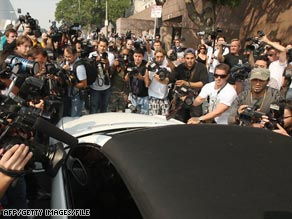 Photographers swarm a car carrying Britney Spears after a Los Angeles court appearance in October 2007.