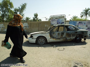 A woman walks past a burned car in September 2007 after an incident involving Blackwater security guards.