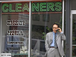 An unidentified man talks on a cell phone in front of the Chung family's shop, Custom Cleaners.