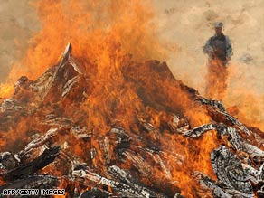 A guard watches over a pile of burning drugs in Kabul, Afghanistan, on June 25, 2008.