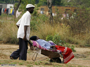 A man from Zimbabwe wheels his sick relative to a cholera clinic.