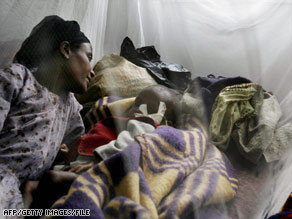A woman lies next to her sick child at a medical center in Sheshemene, Ethiopia, in July.