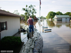 Rex Hipes walks on a sandbag wall Wednesday as Clarksville, Missouri, battles a rising Mississippi River.