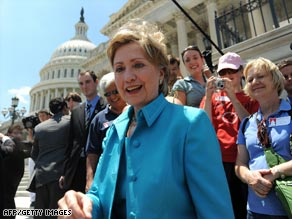 Sen. Hillary Clinton is greeted with cheers as she returns to the Senate after a two-week vacation.