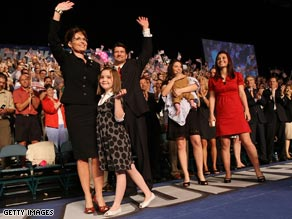 Bristol Palin, second from right, holds infant brother Trig at Friday's announcement of their mother's candidacy.
