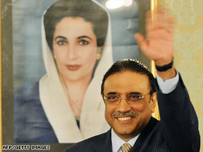Pakistani President Asif Ali Zardari waves in front of a portrait of his wife, the late Benazir Bhutto.