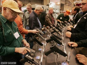 Gun enthusiasts look over pistols during a National Rifle Association event in St. Louis, Missouri, in 2007.