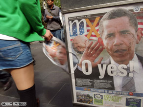 A member of the public picks up a copy of a newspaper with U.S. President-elect Barack Obama on the cover in Sydney, Australia