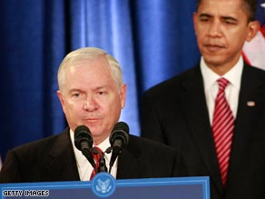 Defense Secretary Robert Gates stands at the microphones as President-elect Barack Obama looks on.