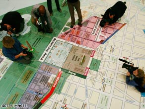 Members of the media inspect an inauguration planning map at the DC Armory in Washington on Thursday.