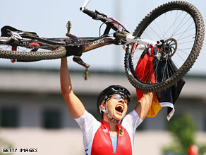 Sabine Spitz of Germany celebrates her victory in the women's mountain bike on Saturday.