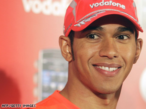 Lewis Hamilton smiling in red baseball cap