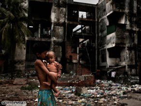 A boy holds a baby in a street in a Shanty town in Phnom Penh, Cambodia. One third of Cambodia's population live in poverty.