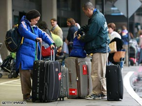 Travelers gather their luggage before checking in for a flight at San Francisco International Airport Tuesday.
