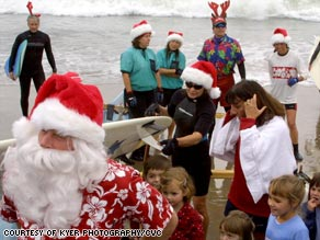 Children in Santa Cruz, California, greet Santa after he arrives on a surf board.