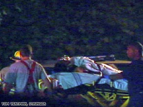 Paramedics carry one of the passengers on a gurney after the Saturday night helicopter crash.