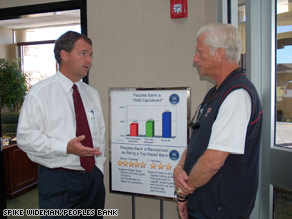 Peoples Bank President Todd McKee, left, chats with customer Tommy McVay on Friday in Lubbock, Texas.