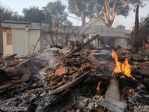 The remains of a home in Montecito, California, smolder Friday outside another home spared by the wildfire.