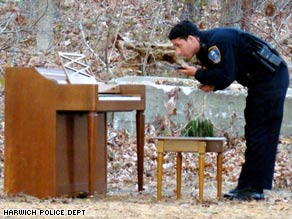 A police officer examines an oddly placed piano in the woods of Harwich, Massachusetts.