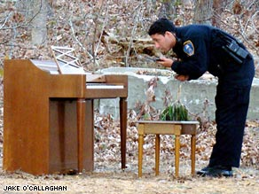 Officer Derek Dutra of the Harwich Police Department examines the mystery piano in the Massachusetts woods.