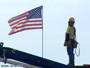 An ironworker looks at the unfurled American flag he placed atop a new building.