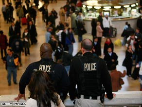 Police watch over travelers at New York's Grand Central Terminal before Thanksgiving.
