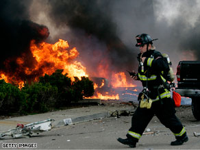 Firefighters and military personnel sift through wreckage Monday in San Diego, California.