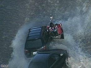 A rescuer uses a boat to reach a driver. At least 15 motorists were rescued after Tuesday's water main break.