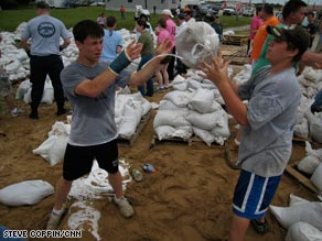 April Dzubic, right, facing forward, of St. Louis, Missouri, passes a sandbag in Winfield on Friday.