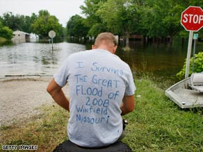 James Burt sits on an embankment near a neighborhood inundated with floodwaters in Winfield, Missouri.