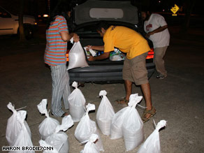 Dwayne Nickles, center, loads sandbags into the trunk of his car with Harsha Dissanayake, left.