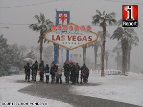 A group in awe of the snow gathers at the iconic Vegas welcome sign.