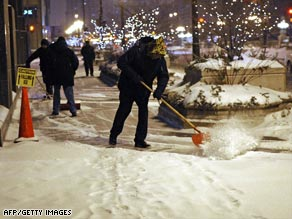 A worker shovels snow as the storm hits Chicago, Illinois.