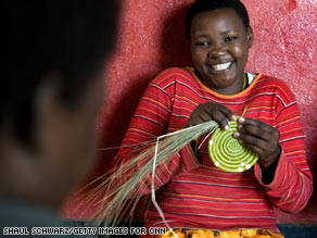 A woman makes the base of a basket at a workshop where Hutus and Tutsis work together.