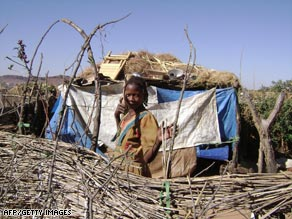 A refugee from the western Sudanese region of Darfur stands in front of a makeshift hut.