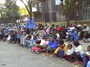 People seeking refuge sit on a curb and sidewalk outside the U.S. Embassy in Harare on Thursday.