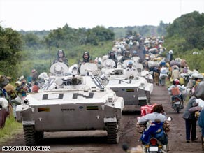 U.N. vehicles on Monday pass between lines of civilians fleeing fighting north of Goma, Congo.
