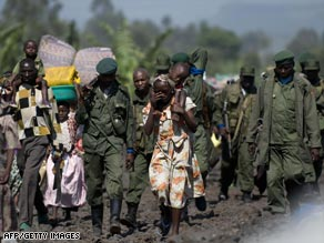 Congolese soldiers and displaced civilians move into Goma on Wednesday, fleeing advancing rebels.