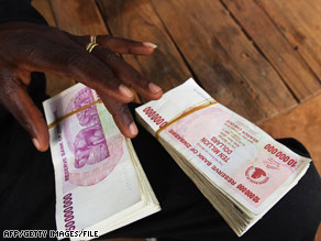 A money-changer in Mozambique holds Zimbabwean $10 million and $50 million bills in May.