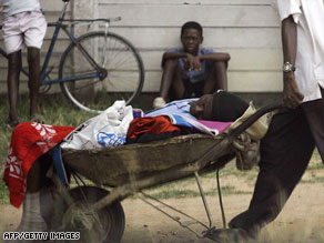 A man carries a relative in a wheelbarrow to a cholera clinic in Harare on Tuesday.
