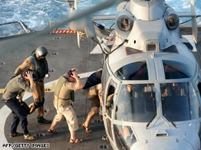 Three British security guards board a helicopter to be transferred to a Royal Navy vessel.