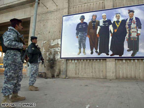 Iraqi soldiers on Monday look at a poster in Kirkuk depicting the region's various ethnic groups.
