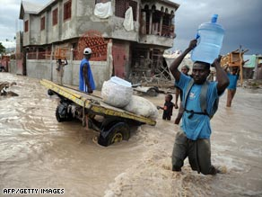 A man carries drinking water through the flooded streets of Gonaives, Haiti, last month.